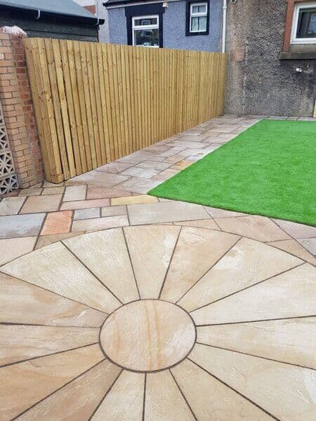large back garden with sandstone slabs and new fence
